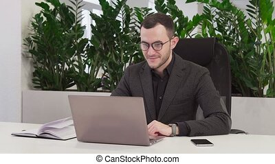 Happy business man with glasses looks at the laptop