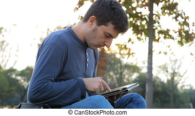 man working with tablet in park