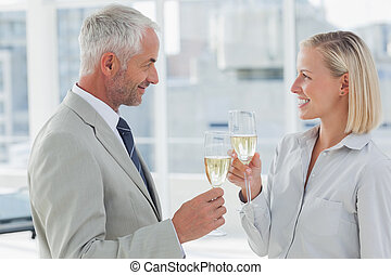 Happy business partners celebrating with champagne