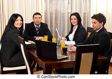Happy business people at meeting table