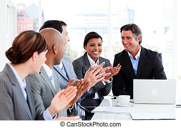 Happy business people clapping in a meeting