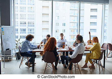 Happy business people gathered around table in office