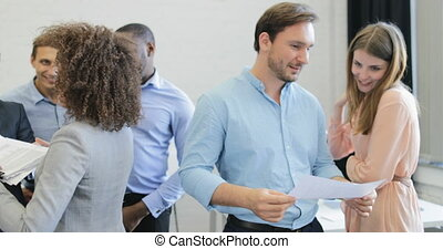 Happy Business People Group Cheering To Good Result Studing Reports On Meeting, Team Of Businesspeople Discussing Documents In Modern Coworking Center