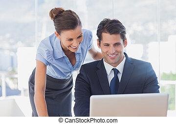 Happy business people looking at laptop and smiling
