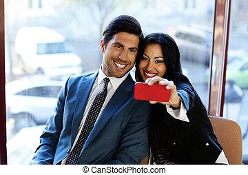 Happy business people making selfie in office