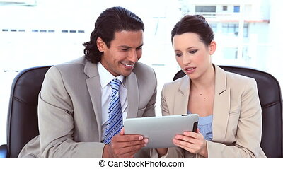Happy business people using a digital computer
