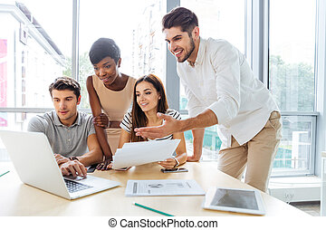 Happy business people using laptop and working together in office