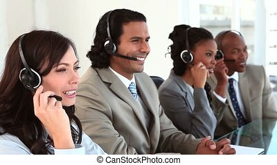 Happy business people using their headsets
