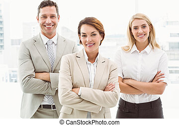Happy business people with arms crossed in office