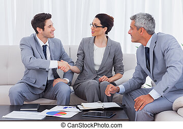 Happy business people working and talking together on sofa