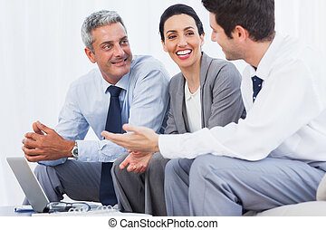 Happy business people working with their laptop on sofa