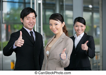 Happy business team giving thumbs up.