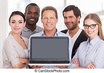 Happy business team. Group of cheerful business people in casual wear standing close to each other while mature man showing laptop monitor and smiling