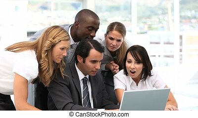 Video of a happy business team looking at a computer