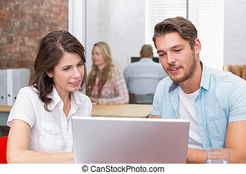 Happy business team looking at computer screen together