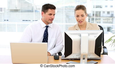 Happy business team looking at computer