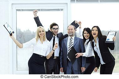 happy business team raising hands, rejoicing.the concept of success