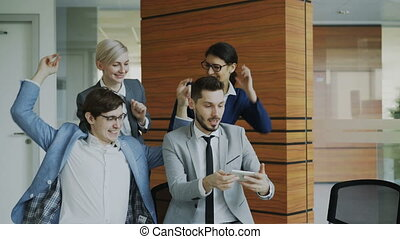 Happy business team taking selfie portrait on smartphone camera and posing for group photo during meeting in modern office