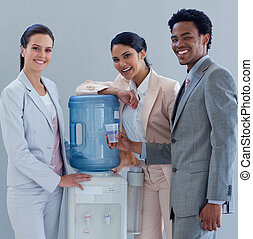 Business team smiling to the camera next to a water cooler in office