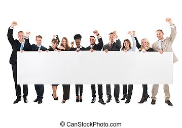 Happy Business Team With Arms Raised Holding Blank Billboard