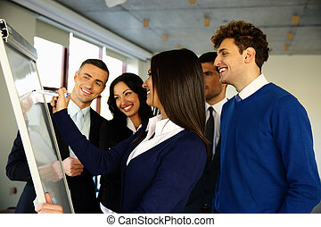 Happy business team with flip board in office