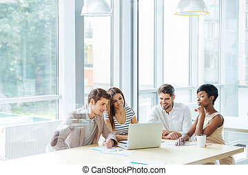 Happy business team working with laptop together in office