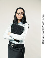 Happy business woman / assistant / secretary portrait. Girl clasping folder to breast. Wearing shirt, skirt and glasses. One of a series.