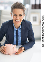 Happy business woman feeding piggy bank with coin