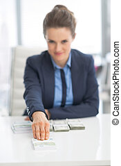 Happy business woman giving money pack