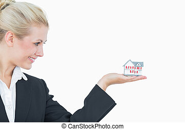 Happy business woman holding model house
