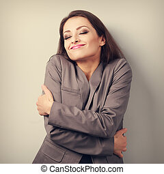 Happy business woman hugging herself with closed eyes and natural emotional face. Love concept of yourself. Toned portrait