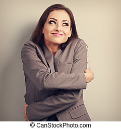 Happy business woman hugging herself with natural emotional enjoying face and thinking look. Love concept of yourself.