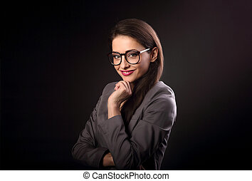 Happy business woman in eyeglasses looking on dark black background with empty copy space. Closeup portrait