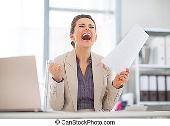 Happy business woman in office rejoicing