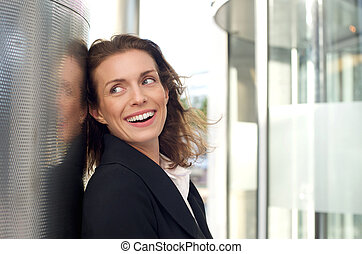 Happy business woman laughing outside