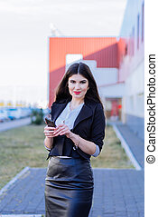 Happy business woman looking at smartphone