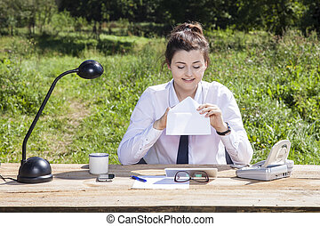 Happy business woman looking at the envelope