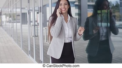 Happy business woman on phone next to window