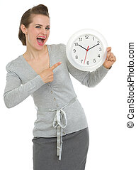 Happy business woman pointing on clock