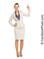 Happy business woman pointing up on copy space