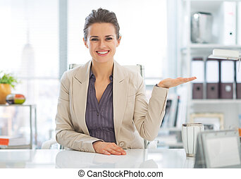 Happy business woman presenting something on empty palm in offic