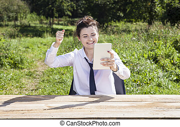 Happy business woman raises her hand in a gesture of success