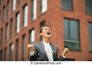 Happy business woman rejoicing in front of office building