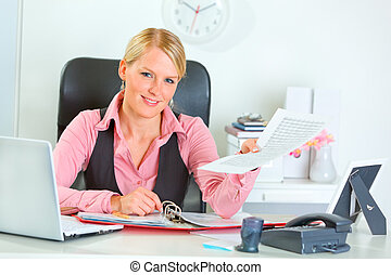 Happy business woman showing document