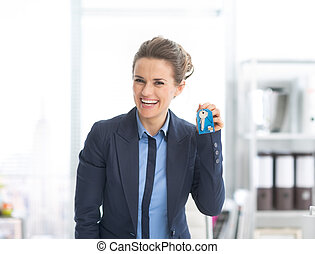 Happy business woman showing keys