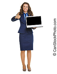 Happy business woman showing laptop blank screen and thumbs up