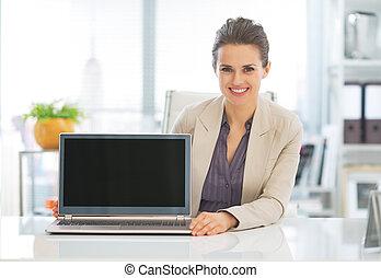 Happy business woman showing laptop blank screen