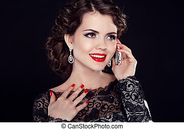Happy Business woman talking on mobile phone. Fashion elegant woman model over dark background.