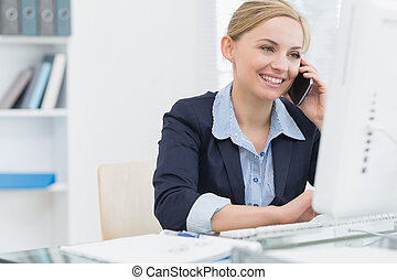 Happy business woman using computer while on call at desk