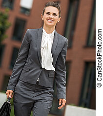 Happy business woman with briefcase walking at office district